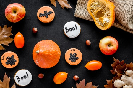 Halloween composition with autumn harvest as dried autumn leaves, pumpkin, apple and round hallooween badges with rats, ghousts, Boo text on black background top view.