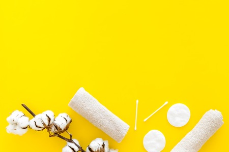 Products made of cotton. Bath accessories. Towels, cotton pads and swabs near dry cotton flowers on yellow background top view copy space