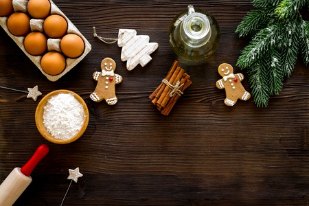Cook homemade gingerbread cookies for New Year party. Rolling pin, eggs, flour, cinnamon near gingerbread man and spruce branch on dark wooden background top view space for text
