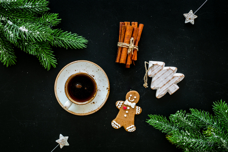 New Year composition with sweets. Gingerbread cookies in shape of man, spruce near coffee, spruce branch, festive decoration on black background top view