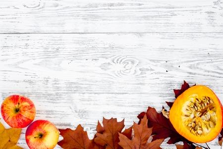 Composición con verduras de otoño y hojas en colores rojo y naranja. Hojas secas marrones, calabaza, manzana en la vista superior de fondo de madera blanca. Foto de archivo