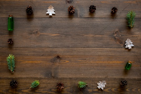 New Year frame made of pine sprigs, cones, spruce figure, fir oil on dark wooden background top view.