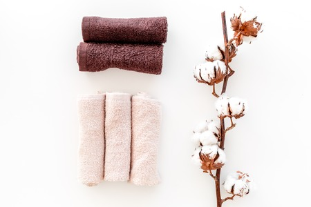 Cotton towels high quality. Set of towels twisted coil near dry cotton flowers on white background top view.