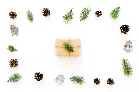New Year gift decorated with craft paper and pine sprout in frame of spruce branch, pine cones, spruce cutout on white background top view.