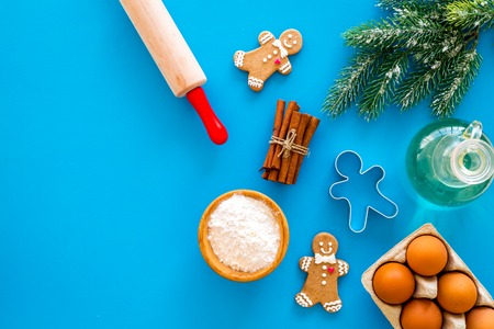 Cook homemade gingerbread cookies for New Year party. Rolling pin, eggs, flour, cinnamon near gingerbread man and spruce branch on blue background top view.