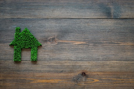 Eco friendly technologies for home concept. House silhouette made of green grass on dark wooden background top view.