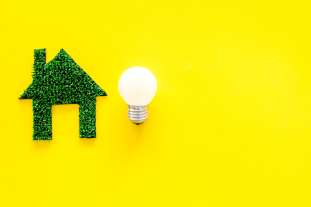 Enegry saving technology concept. House cutout made of green grass near light bulb on yellow background top view. Banco de Imagens