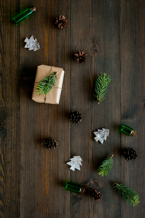 New Year pattern with pine sprigs, cones, spruce figure, fir oil and new year gift decorated with craft paper and pine sprout on dark wooden background top view. Imagens