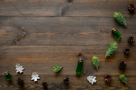 Winter ornament, New Year pattern. Pine sprigs, cones, spruce figure, fir oil on dark wooden background top view copy space Stock Photo