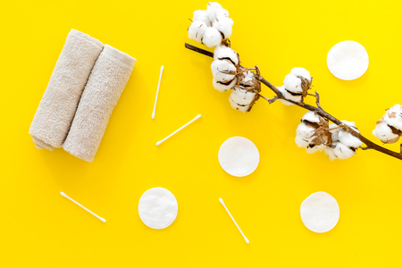 Cotton hygiene products. Cotton pads and swabs, towels twisted coil near dry cotton flowers on yellow background top view