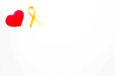 Endometriosis. Gynecological diseases concept. Symbolic yellow ribbon near heart sign on white background top view copy space