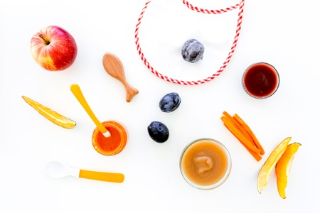 Ingredients for baby puree. Assortment of flavors of baby food. Vegetables and fruits. Apple, carrot, pumpkin, prune near bib on white background top view