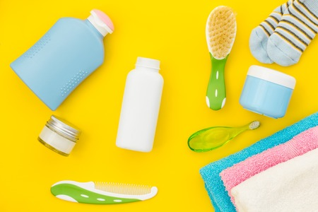 Baby care. Bath cosmetics and accessories for child. Shampoo, gel, cream, teeth brush, comb on yellow background top view.