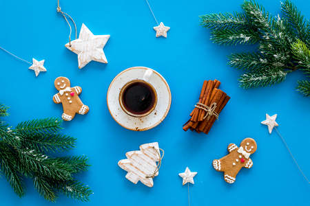 New Year gingerbread cookies. Gingerbread man near coffee, spruce branch, festive decoration on blue background top view.