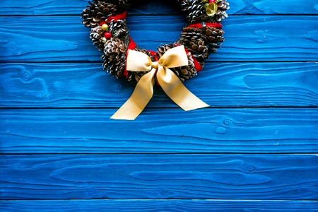 Christmas wreath made of pine cones on blue wooden background top view.