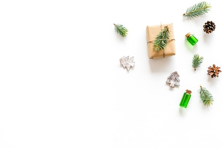 Composition with New Year gift wrapped in craft paper and decorted with pine sprout near pine sprigs, cones, spruce figure, fir oil on white background top view. Stok Fotoğraf