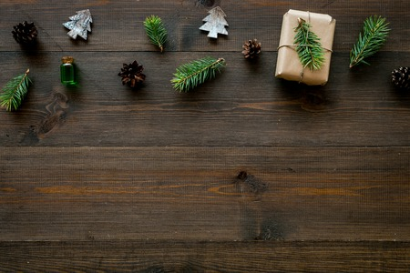 Background with New Year gift. Box wrapped in craft paper, decorated with pine sprig and cones on dark wooden background top view.