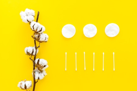 Products made of cotton. Bath accessories. Towels, cotton pads and swabs near dry cotton flowers on yellow background top view.