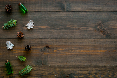 Winter ornament, New Year pattern. Pine sprigs, cones, spruce figure, fir oil on dark wooden background top view. Stock Photo