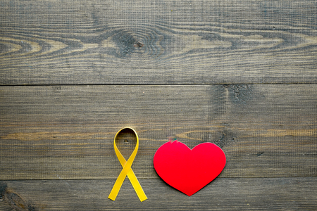 Endometriosis. Gynecological diseases concept. Symbolic yellow ribbon near heart sign on dark wooden background top view.