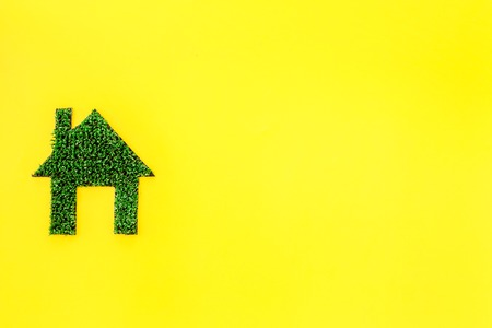 Eco friendly technologies for home concept. House silhouette made of green grass on yellow background top view. Imagens