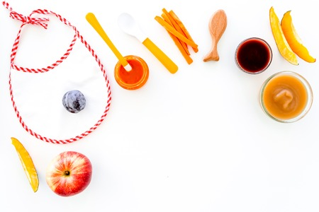 Ingredients for baby puree. Assortment of flavors of baby food. Vegetables and fruits. Apple, carrot, pumpkin, prune near bib on white background top view. Stock Photo