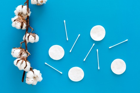 Bath accessories. Products for remove cosmetics. Cotton swabs and cotton pads on blue background top view. 스톡 콘텐츠
