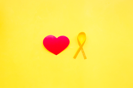 Endometriosis. Gynecological diseases concept. Symbolic yellow ribbon near heart sign on yellow background top view.