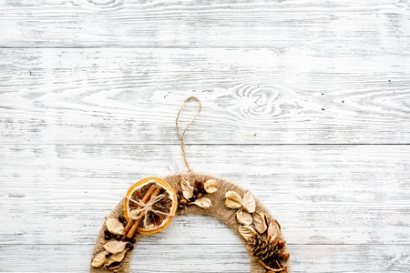 Creative, unusual christmas wreath made of thread, dry fruits and nuts on white wooden background top view.