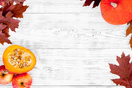 Composition with autumn vegetables and leaves in red and orange colors. Brown dried leaves, pumpkin, apple on white wooden background top view.