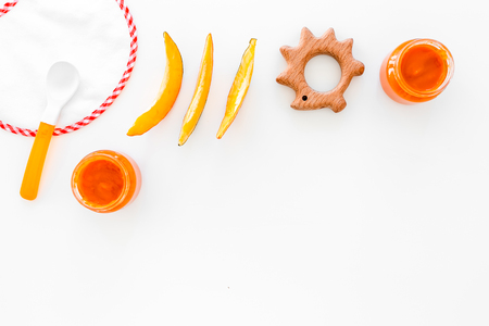 Baby food concept. Pumpkin puree in bowl near bib, pumpkin slices, spoon on white background top view. Stock Photo