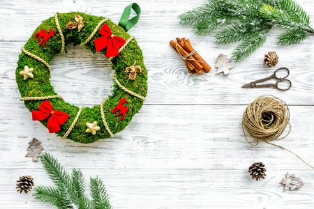 Process of making christmas wreath concept. Green christmas wreath near matherials and instruments, sciccors on white wooden background top view. Stock Photo
