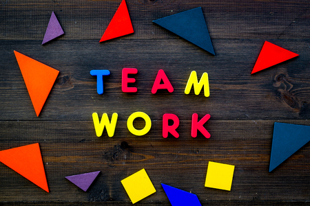 Teamwork concept. Teamwork techniques for students. Text teamwork lined with colored letters in abstract colored frame on dark wooden background top view. Stock Photo