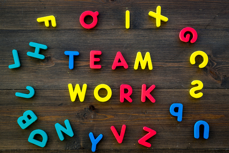 Teamwork training concept. Text teamwork lined with colored letters in frame of toy letters on dark wooden background top view. Stock Photo