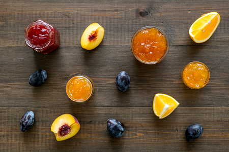 Jams different tastes made of fruits and berries near pieces of fruits on dark wooden background top view.