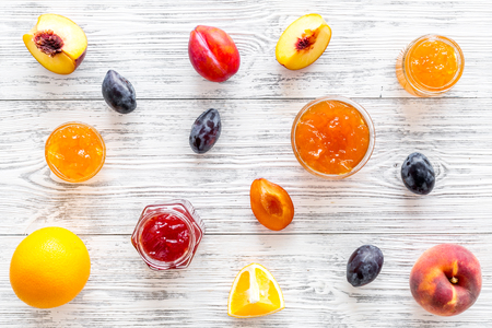 Jams different tastes made of fruits and berries near pieces of fruits on white wooden background top view.