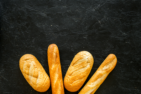 Loaf of white bread and baguette on black background top view.