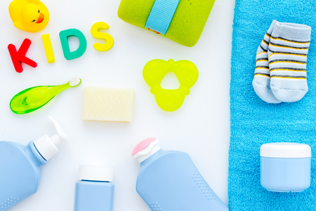 Shower accessories for child. Set with shampoo, towel, soap, gel, towel, brush and yellow rubber duck on white background top view.