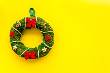 Christmas wreath traditional, classic type. Wreath made of spruce branches and red ribbons on yellow background top view.