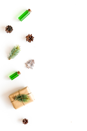 Composition with New Year gift wrapped in craft paper and decorted with pine sprout near pine sprigs, cones, spruce figure, fir oil on white background top view. Stock Photo