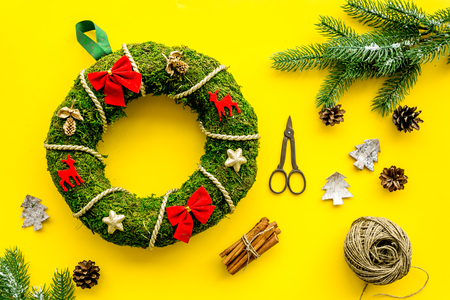 Preparing to Christmas. Traditional green christmas wreath near decorative elements on yellow background top view.