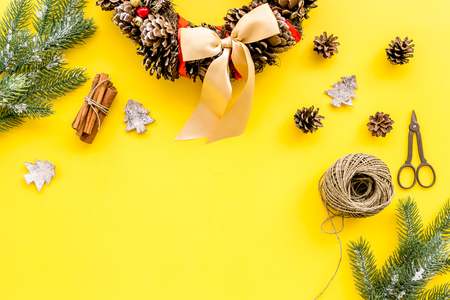 Process of making christmas wreath concept. Christmas wreath made of pine cones near matherials and instruments, sciccors on yellow background top view.