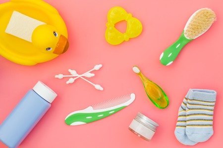 Shower accessories for child. Set with shampoo, towel, soap, gel, towel, brush and yellow rubber duck on pink background top view pattern.