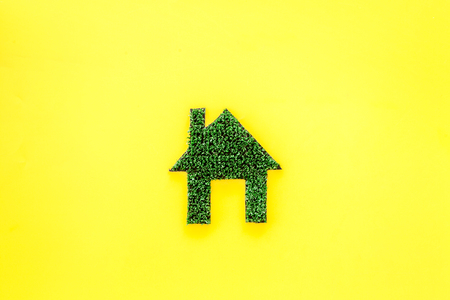 Eco friendly technologies for home concept. House silhouette made of green grass on yellow background top view. Stock Photo