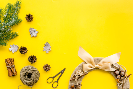 Preparing to Christmas. Creative christmas wreath made of thread near decorative elements on yellow background top view.