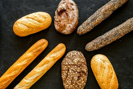 Set of fresh homemade bread. Bread assortment. Loaf, baguette. White and brown bread on black background top view.