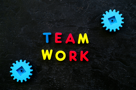 Teamwork concept. Text teamwork lined with colored letters near toy gears on black background top view.