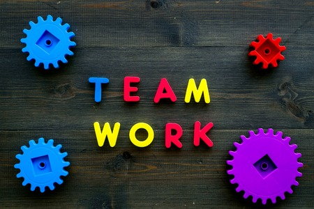 Teamwork concept. Text teamwork lined with colored letters near toy gears on dark wooden background top view. Stock Photo