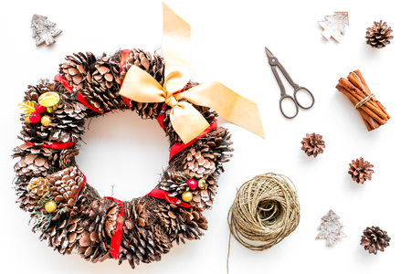 Preparing to Christmas. Christmas wreath made of pine cones near decorative elements on white background top view.