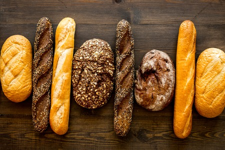 Set of fresh homemade bread. Bread assortment. Loaf, baguette. White and brown bread on dark wooden background top view. Stock Photo